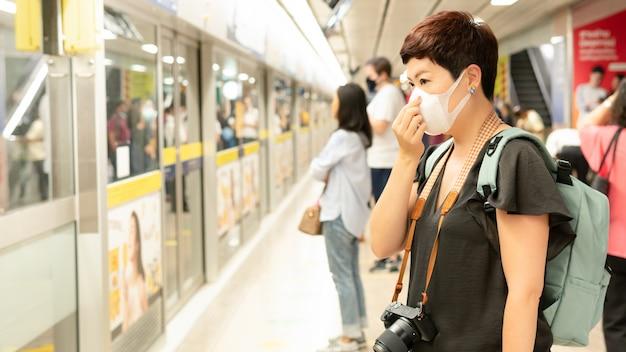 Piękna podróżniczka z azji w średnim wieku pokrywa usta i kaszel, nosi maskę medyczną w celu ochrony przed infekcją wirusami, pandemią, wybuchem i epidemią chorób w zatłoczonym pociągu podziemnym