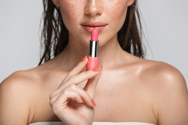 Piękna pół twarzy portret atrakcyjnej zmysłowej młodej kobiety z mokrą brunetką, długimi włosami, stojącą na szarym tle, pokazując różową szminkę