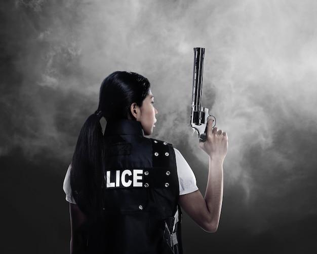Piękna policyjna kobieta trzyma pistolet