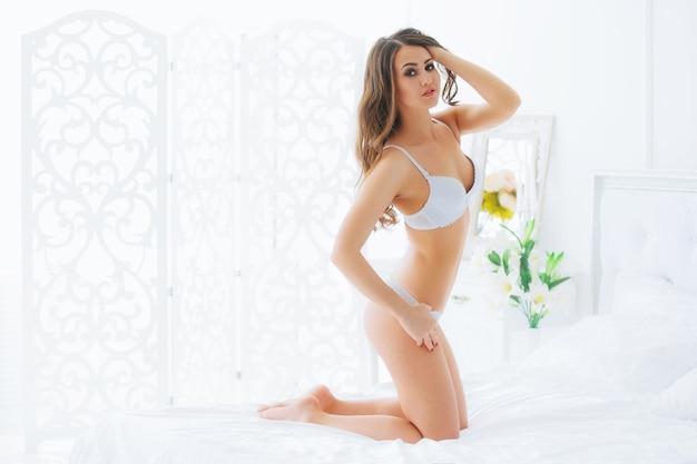 Piękna, ponętna młoda kobieta w białej seksownej bieliźnie siedzi na białym łóżku