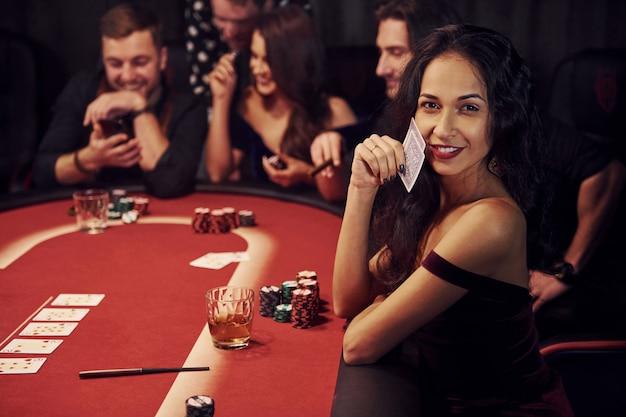 Piękna portret kobiety grupa eleganckich młodych ludzi grających razem w pokera w kasynie