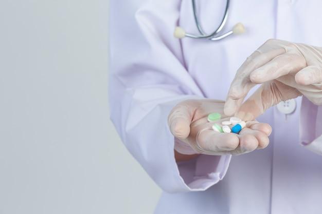 Piękna potomstwo lekarka jest ubranym maskę podczas gdy trzymający medycynę z gumowymi rękawiczkami na szarości ścianie.
