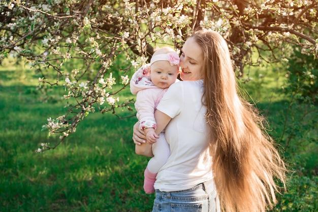 Piękna potomstwo matka trzyma dziecka w jej rękach na kwiatonośnym drzewie. pielęgnacja włosów podczas laktacji