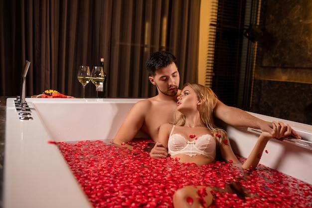 Piękna potomstwo para cieszy się skąpanie z różanymi płatkami