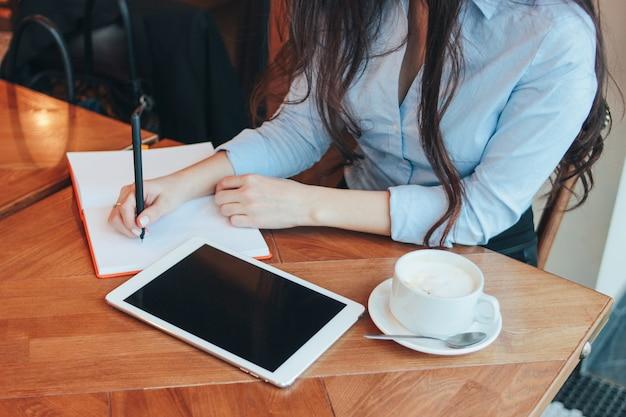 Piękna powabna brunetki dziewczyna z pastylką przy stołem w kawiarni