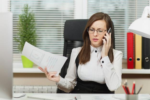 Piękna poważna biznesowa kobieta w garniturze i okularach siedząca przy biurku, pracująca przy współczesnym komputerze z dokumentami w jasnym biurze, rozmawiająca przez telefon komórkowy, rozwiązująca problemy, patrząca na bok