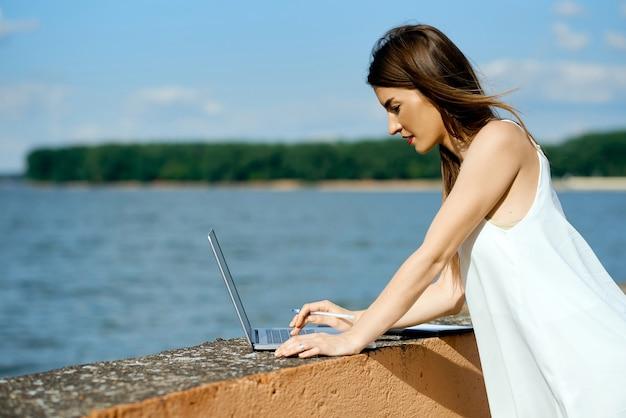Piękna, poważna dziewczyna w białej sukni z tabletem, długopisem, laptopem na stacji dokującej. zdjęcie wysokiej jakości