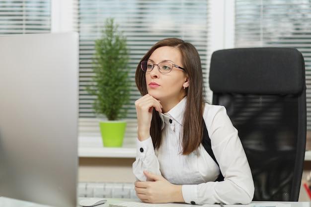 Piękna poważna i pochłonięta biznesowa kobieta o brązowych włosach w garniturze i okularach siedząca przy biurku z tabletem, pracująca przy komputerze z nowoczesnym monitorem z dokumentami w jasnym biurze, patrząca na bok