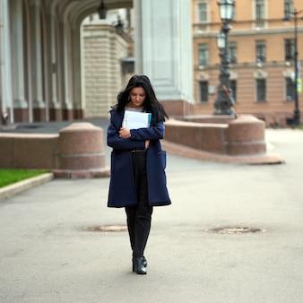 Piękna poważna inteligentna dziewczyna brunetka studentka trzyma zeszyty i podręczniki, idzie na uniwersytet