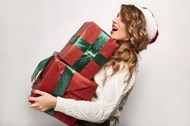 Piękna pozytywna blondynka w swetrze i świątecznej czapce