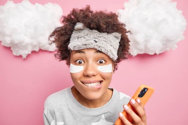 Piękna pozytywna kobieta gryzie usta radośnie patrzy na aparat używa telefonu komórkowego do surfowania w sieciach społecznościowych ubrana w bieliznę nocną odizolowaną na różowej ścianie. dzień dobry.
