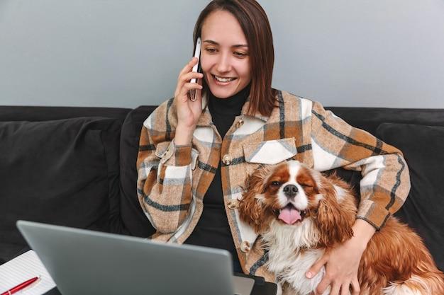 Piękna pozytywna kobieta rozmawia przez telefon komórkowy i przytula psa siedząc na kanapie w domu
