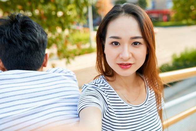 Piękna pozytywna młoda azjatycka kobieta biorąca selfie na zewnątrz