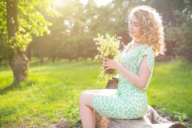 Piękna pozytywna młoda kobieta w zielonej sukience leży na zielonej trawie z polnymi stokrotkami i trzyma bukiet ze stokrotkami w dłoniach.