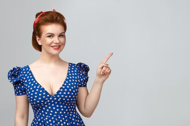 Piękna pozytywna młoda modelka ze stylową fryzurą i efektownym makijażem patrząc na kamerę z uroczym szczęśliwym uśmiechem, wskazując palcem wskazującym na pustą ścianę z miejscem na kopię reklamy