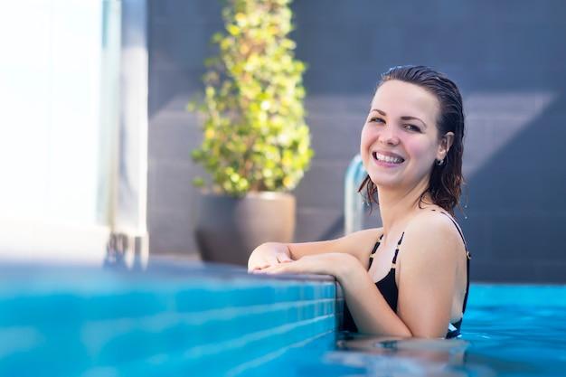Piękna pozytywna rozochocona dziewczyna, młodej kobiety uśmiechnięta pozycja, cieszący się, relaksujący w wodzie, pływacki basen outdoors w hotelu