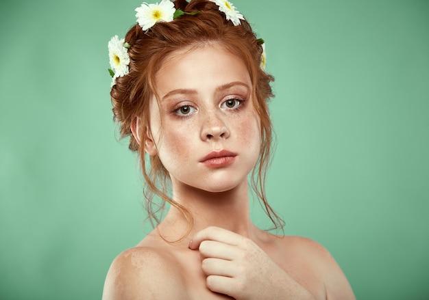 Piękna pozytywna rudowłosa dziewczyna z koroną rumianku na głowie