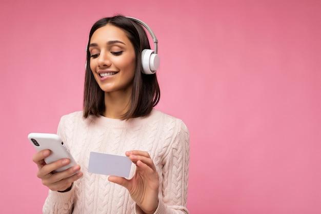 Piękna pozytywna uśmiechnięta młoda brunetka kobieta ubrana w różowy sweter dorywczo na białym tle