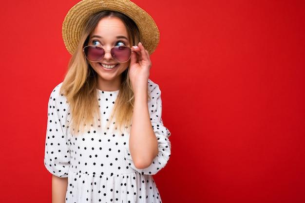 Piękna pozytywna uśmiechnięta szczęśliwa radosna młoda blondynka na sobie letnie ubranie i stylowe okulary przeciwsłoneczne na białym tle
