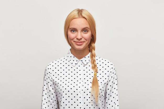 Piękna pracowita blondynka o niebieskich oczach, warkocz, czuje się szczęśliwa, czule się uśmiecha, nosi białą koszulę w czarne kropki
