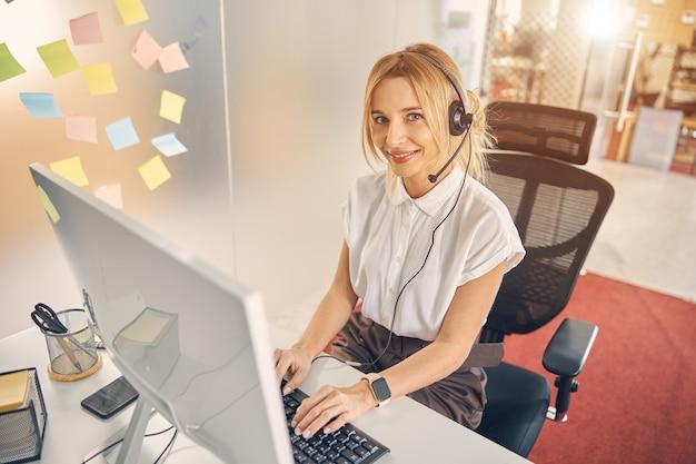 Piękna pracownica w słuchawkach uśmiecha się siedząc przy stole z komputerem stacjonarnym w biurze