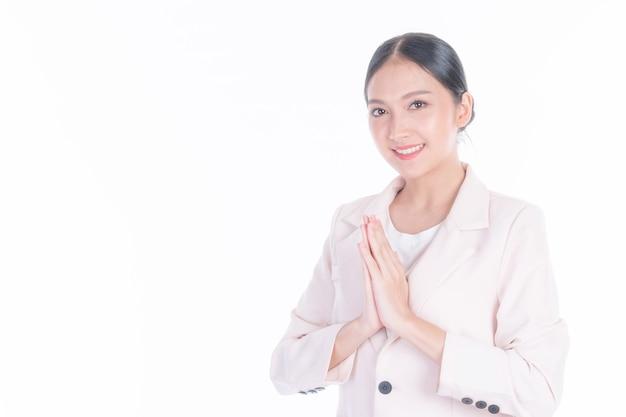 Piękna pracująca azjatka okazują szacunek, symbol sawasdee z kultury powitania tajlandii