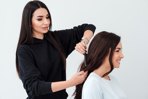 Piękna profesjonalna stylistka tworzy fryzurę dla swojego kochanego klienta