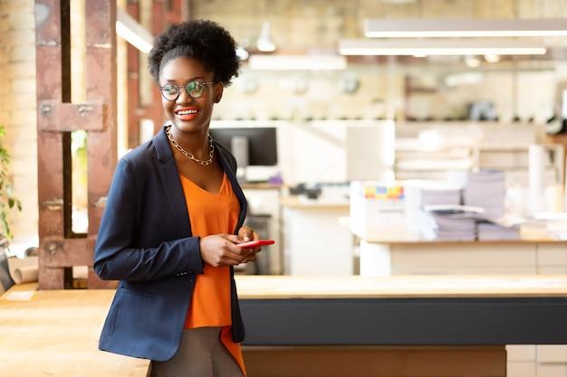 Piękna projektantka. piękna afroamerykańska projektantka nosząca stylowy naszyjnik trzymający telefon