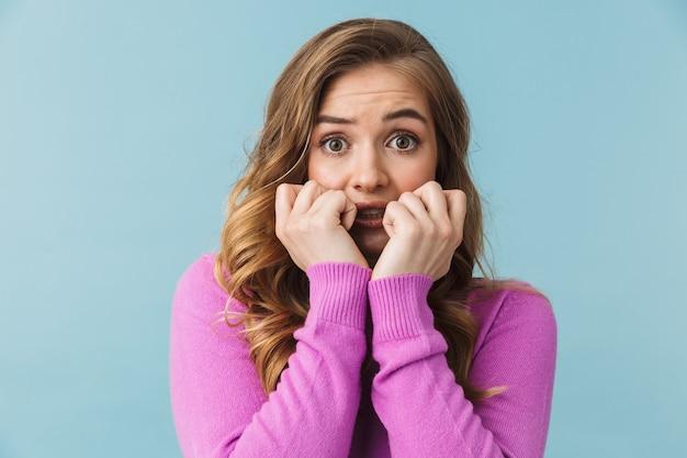 Piękna przestraszona młoda dziewczyna nosi zwykłe ubrania, stojąc na białym tle nad niebieską ścianą, zakryj twarz