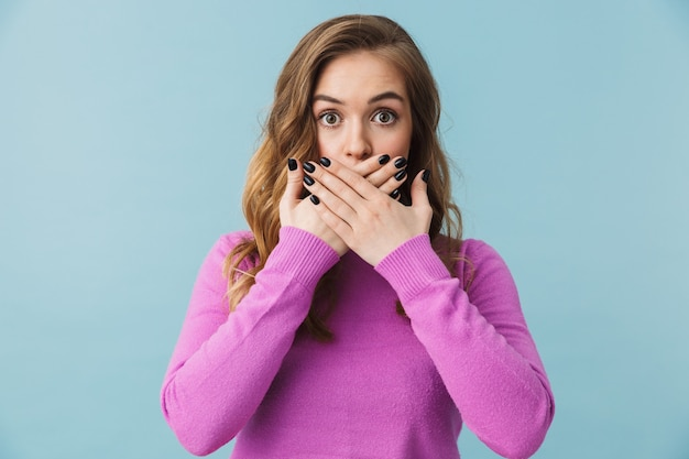 Piękna przestraszona młoda dziewczyna nosząca zwykłe ubrania stojąca na białym tle nad niebieską ścianą, zakrywająca usta