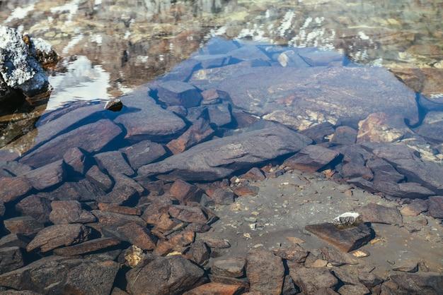Piękna przyroda tło kamieniste dno w przezroczystej wodzie jeziora polodowcowego w słońcu. słoneczny charakter tło z wieloma kamieniami w czystej wodzie jeziora lodowcowego. niewidzialna woda górskiego jeziora.