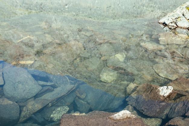 Piękna przyroda tło kamieniste dno w przezroczystej wodzie jeziora polodowcowego w słońcu. słoneczny charakter tło z wieloma kamieniami w czystej wodzie jeziora polodowcowego. niewidzialna woda górskiego jeziora.