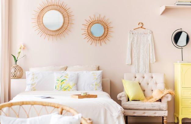 Piękna, przytulna nowoczesna sypialnia z dużym łóżkiem, komodą, fotelem i elementami dekoracyjnymi, utrzymana w jasnej kolorystyce. poziome zdjęcie