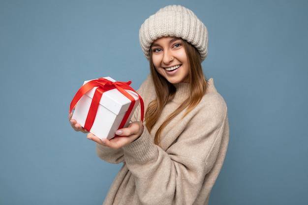 Piękna radosna uśmiechnięta ciemna blondynka młoda osoba płci żeńskiej na białym tle