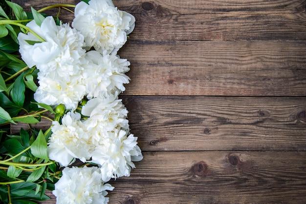 Piękna rama białych piwonii na drewnianym rustykalnym tle, widok z góry