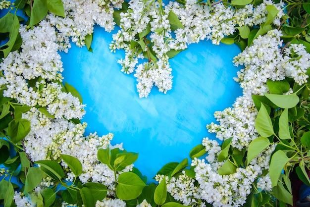 Piękna rama w kształcie serca wykonana z białego bzu na niebieskiej powierzchni