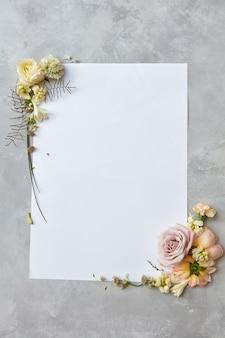 Piękna ramka z kwiatami i białym papierem z miejscem na tekst na szarym betonowym tle, płaskie lay