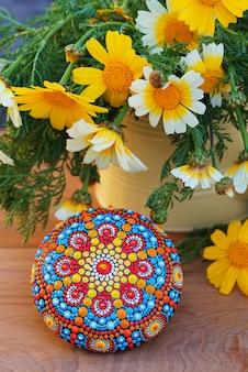 Piękna ręcznie malowana mandala w pobliżu kwiatów