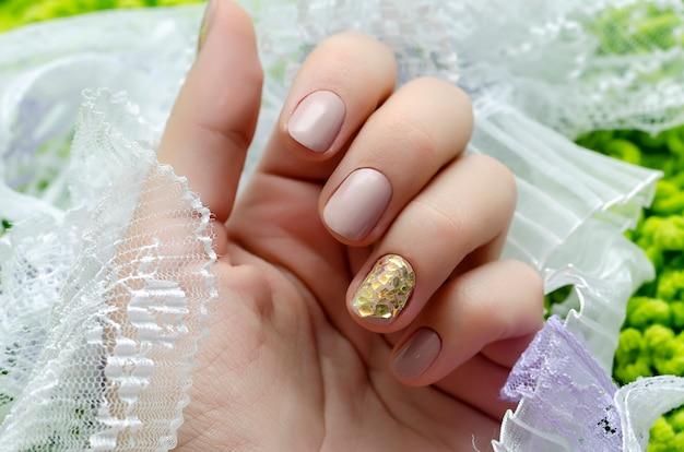 Piękna ręka z beżowym wzorem do paznokci.