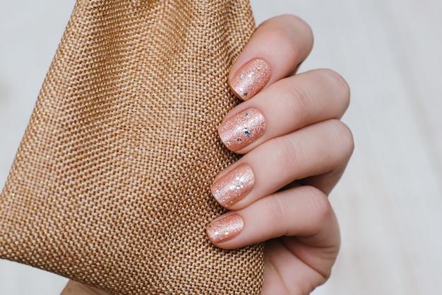 Piękna ręka z ciemnoróżowym wzorem do paznokci