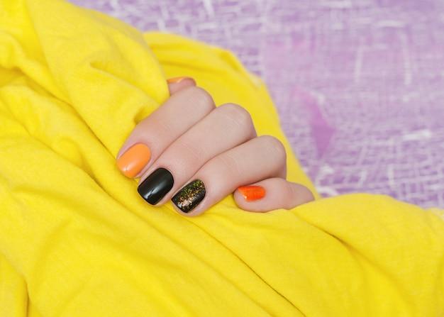 Piękna ręka z pomarańczowymi i czarnymi zdobieniami do paznokci