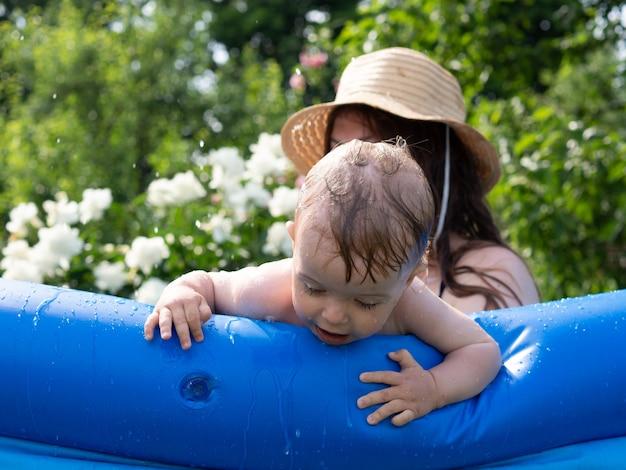Piękna roczna dziewczyna kąpie się i bawi się w nadmuchiwanym basenie z mamą w upalny dzień