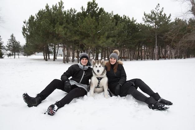 Piękna rodzina, mężczyzna i dziewczyna w zimowym lesie z psem. baw się z psem husky syberyjskim.