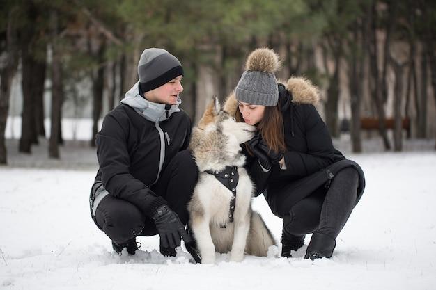 Piękna rodzina, mężczyzna i dziewczyna w zimowym lesie z psem. pobaw się z psem siberian husky.