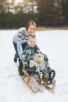 Piękna rodzina młodej matki i syna, ciesząc się śnieżny zimowy dzień na świeżym powietrzu, zabawy na sankach