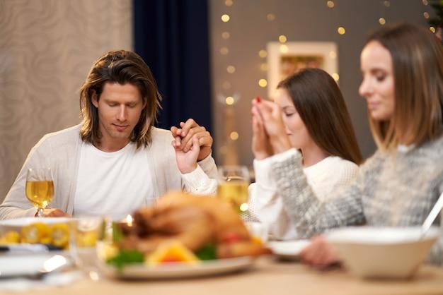 Piękna rodzina modląca się przy świątecznym obiedzie