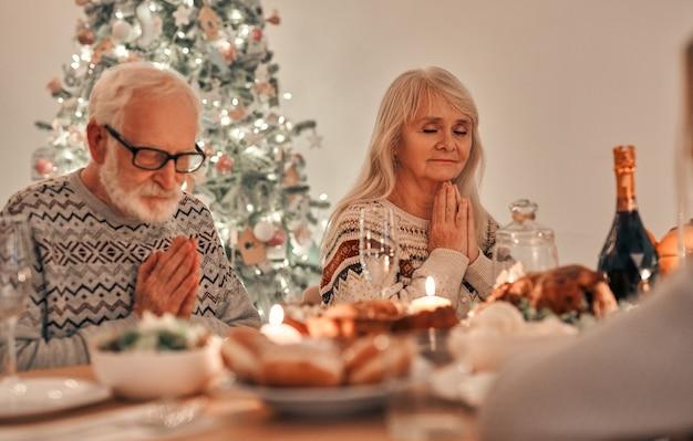 Piękna rodzina modląca się przy świątecznym stole