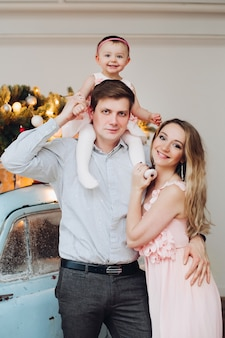 Piękna rodzina pozuje wpólnie blisko błękitnego retro bożenarodzeniowego samochodu.