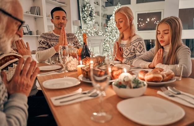 Piękna rodzina siedzi przy świątecznym stole i modli się