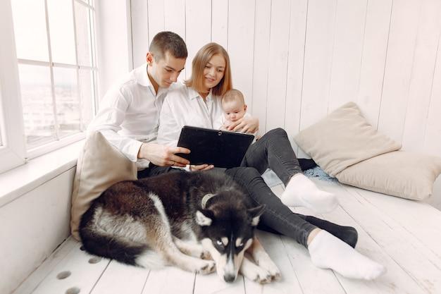 Piękna rodzina spędza czas w sypialni z tabletem